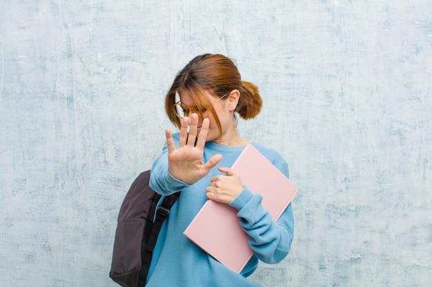Mulher jovem estudante cobrindo o rosto com a mão e colocando a outra mão na frente para parar a câmera, recusando fotos ou imagens contra a parede do grunge