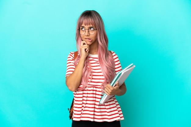 Mulher jovem estudante com cabelo rosa isolado em um fundo azul, tendo dúvidas e pensando