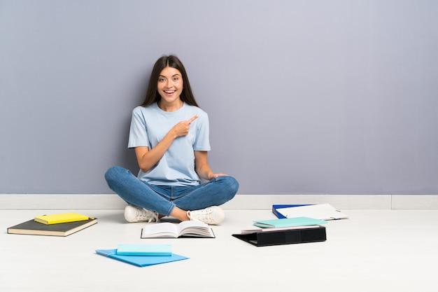 Mulher jovem estudante com muitos livros no chão, apontando o dedo para o lado