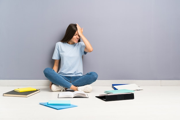 Mulher jovem estudante com muitos livros no chão com dúvidas e com expressão de rosto confuso