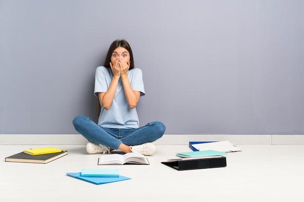 Mulher jovem estudante com muitos livros no chão com expressão facial de surpresa
