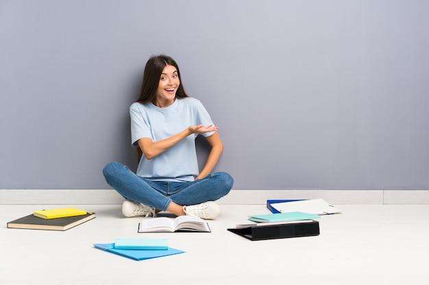 Mulher jovem estudante com muitos livros no chão, estendendo as mãos para o lado para convidar para vir