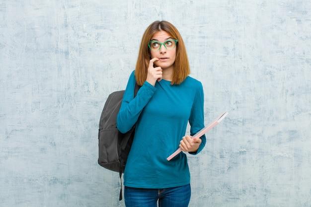 Mulher jovem estudante com olhar surpreso, nervoso, preocupado ou assustado, olhando para o lado em direção a copyspace contra a parede do grunge