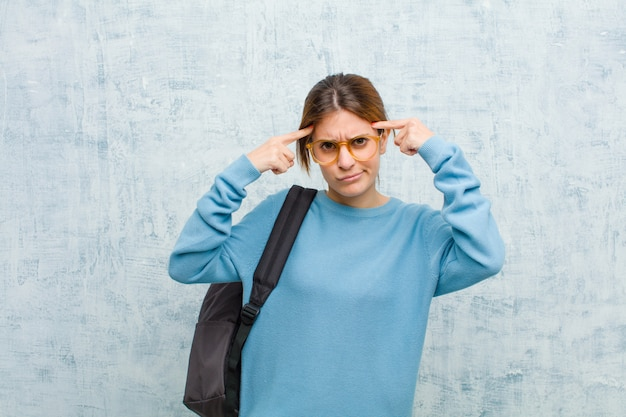 Mulher jovem estudante com um olhar sério e concentrado, fazendo brainstorming e pensando em um problema desafiador