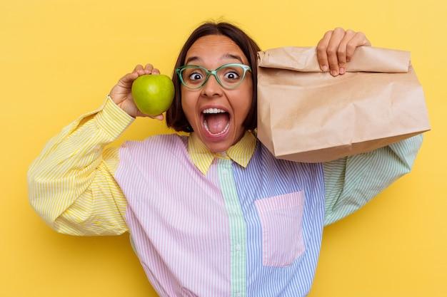 Mulher jovem estudante de raça mista almoçando isolada em fundo amarelo