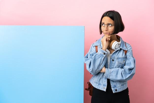 Mulher jovem estudante de raça mista com um grande banner sobre fundo isolado, tendo dúvidas e pensando