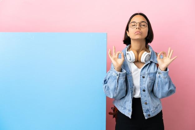 Mulher jovem estudante de raça mista com um grande banner sobre um fundo isolado em pose zen