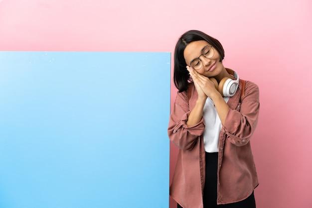 Mulher jovem estudante de raça mista com um grande banner sobre um fundo isolado fazendo gestos de dormir em expressão dorível