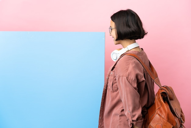 Mulher jovem estudante de raça mista com um grande banner sobre um fundo isolado na posição traseira e olhando para trás