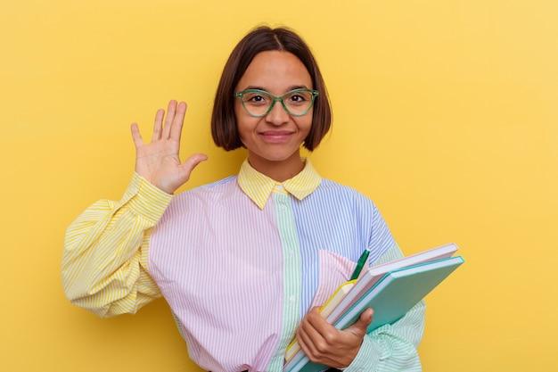 Mulher jovem estudante de raça mista isolada na parede amarela sorrindo alegre mostrando o número cinco com os dedos.