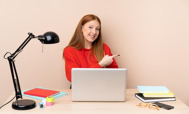 Mulher jovem estudante em um local de trabalho com um laptop apontando para trás