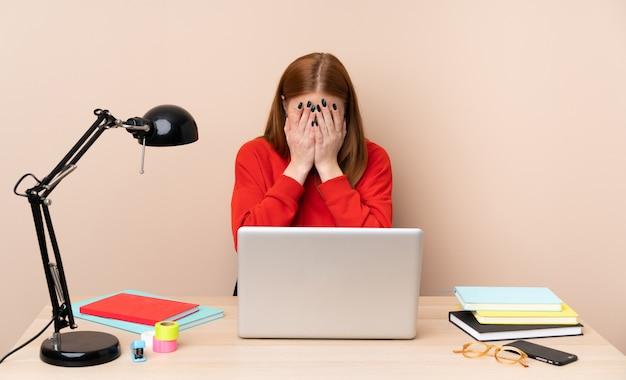 Mulher jovem estudante em um local de trabalho com um laptop com expressão de cansado e doente