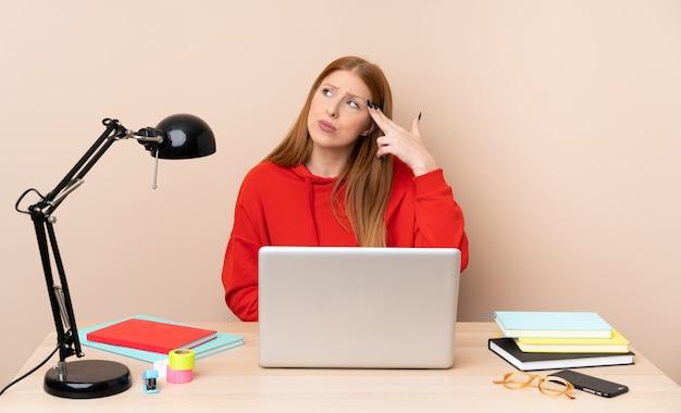 Mulher jovem estudante em um local de trabalho com um laptop com problemas fazendo gesto de suicídio