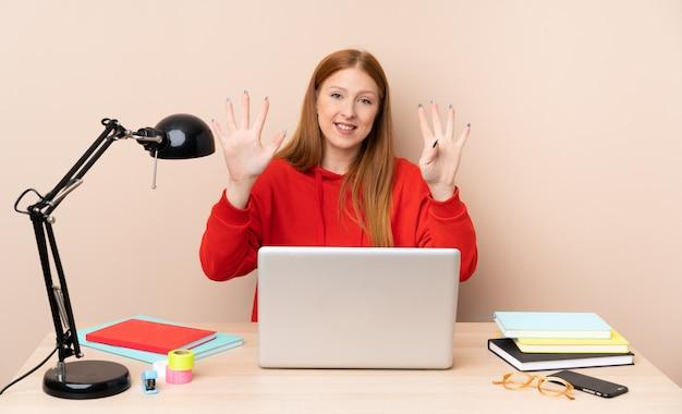 Mulher jovem estudante em um local de trabalho com um laptop, contando nove com os dedos