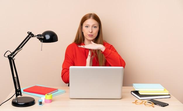 Mulher jovem estudante em um local de trabalho com um laptop, fazendo gesto de intervalo