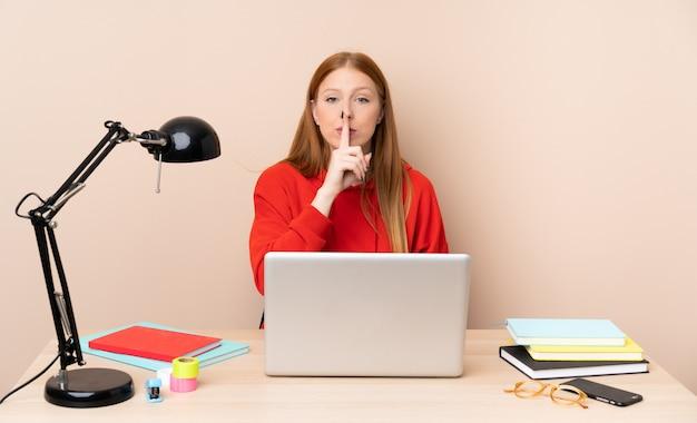 Mulher jovem estudante em um local de trabalho com um laptop, mostrando um sinal de gesto de silêncio colocando o dedo na boca