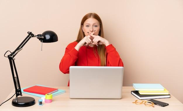Mulher jovem estudante em um local de trabalho com um laptop, mostrando um sinal de gesto de silêncio