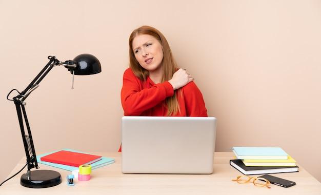Mulher jovem estudante em um local de trabalho com um laptop que sofre de dor no ombro por ter feito um esforço