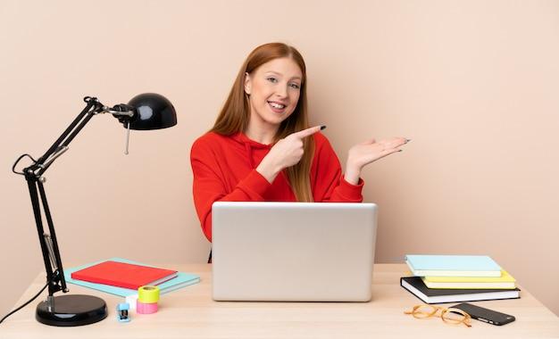 Mulher jovem estudante em um local de trabalho com um laptop segurando copyspace imaginário na palma da mão para inserir um anúncio