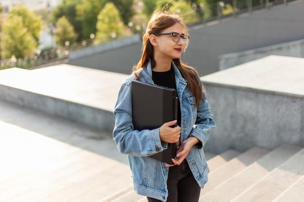Mulher jovem estudante em uma jaqueta jeans e óculos sobe as escadas com um laptop nas mãos na cidade