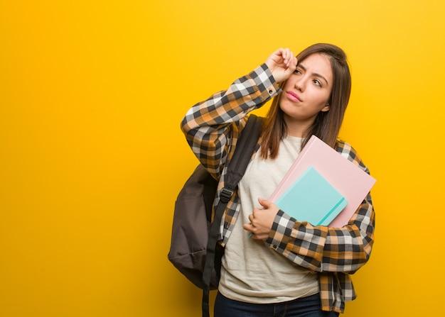 Mulher jovem estudante fazendo o gesto de uma luneta