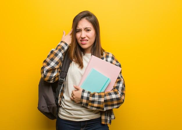 Mulher jovem estudante fazendo um gesto de decepção com o dedo