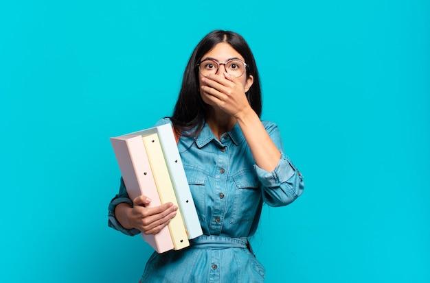 Mulher jovem estudante hispânica cobrindo a boca com as mãos com uma expressão chocada e surpresa, mantendo um segredo ou dizendo oops
