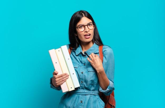 Mulher jovem estudante hispânica com aparência arrogante, bem-sucedida, positiva e orgulhosa, apontando para si mesma
