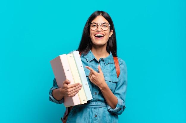 Mulher jovem estudante hispânica parecendo animada e surpresa, apontando para o lado e para cima para copiar o espaço
