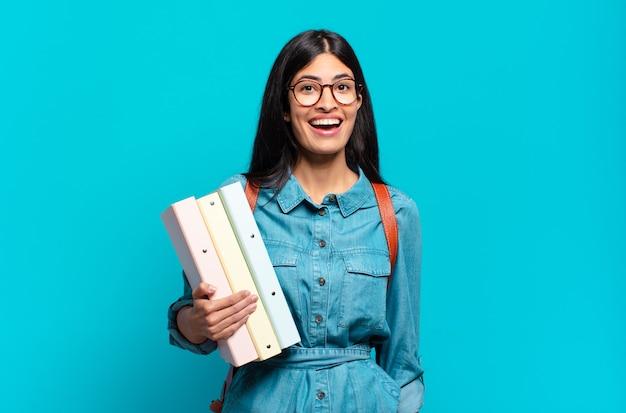 Mulher jovem estudante hispânica parecendo feliz e agradavelmente surpresa, animada com uma expressão de fascínio e choque