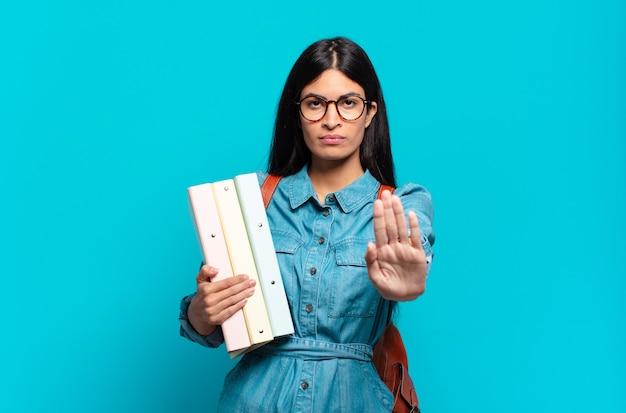 Mulher jovem estudante hispânica parecendo séria, severa, descontente e irritada, mostrando a palma da mão aberta fazendo gesto de pare