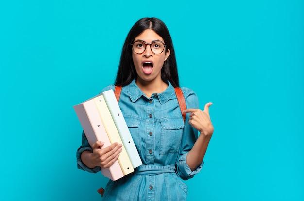 Mulher jovem estudante hispânica se sentindo feliz, surpresa e orgulhosa, apontando para si mesma com um olhar animado e surpreso