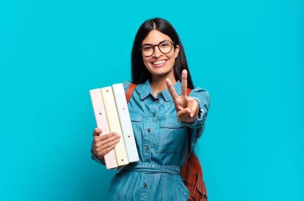 Mulher jovem estudante hispânica sorrindo e parecendo feliz, despreocupada e positiva, gesticulando vitória ou paz com uma mão