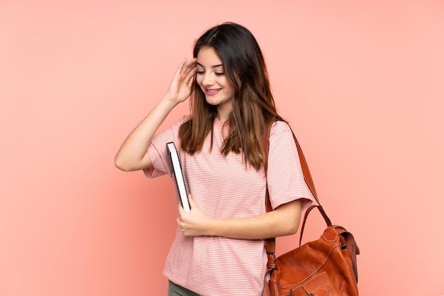 Mulher jovem estudante indo para a universidade sobre parede rosa rindo