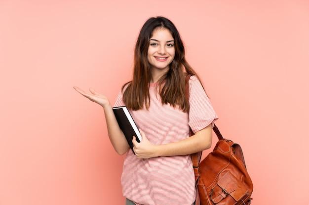 Mulher jovem estudante indo para a universidade sobre parede rosa segurando o espaço em branco imaginário na palma da mão