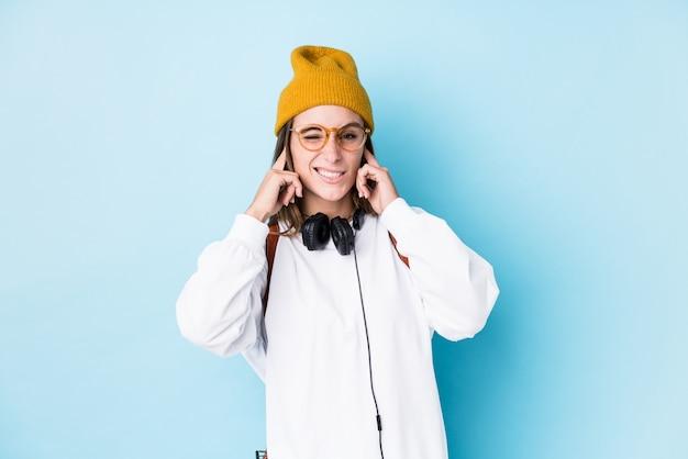 Mulher jovem estudante isolada cobrindo os ouvidos com as mãos.