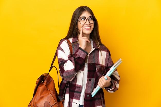 Mulher jovem estudante isolada em um fundo amarelo pensando em uma ideia enquanto olha para cima