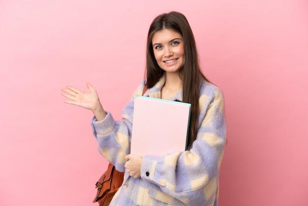 Mulher jovem estudante isolada em um fundo rosa estendendo as mãos para o lado para convidar para vir