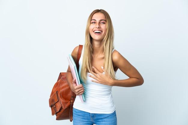Mulher jovem estudante isolada em uma parede branca sorrindo muito