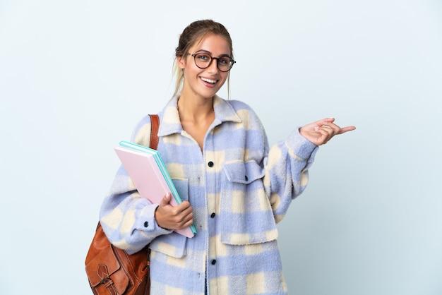 Mulher jovem estudante isolada na parede branca apontando o dedo para o lado
