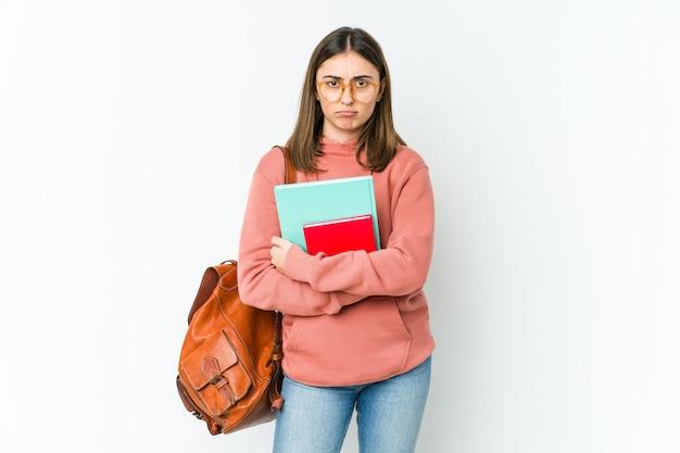 Mulher jovem estudante isolada na parede branca com o rosto franzido de desprazer, de braços cruzados