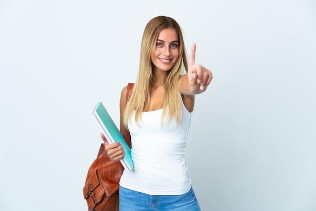 Mulher jovem estudante isolada na parede branca mostrando e levantando um dedo