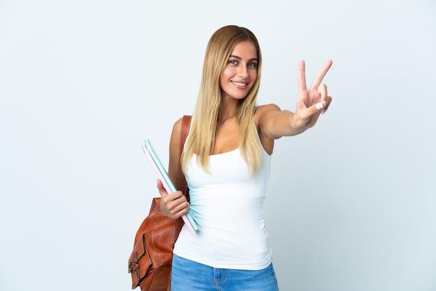 Mulher jovem estudante isolada na parede branca sorrindo e mostrando sinal de vitória