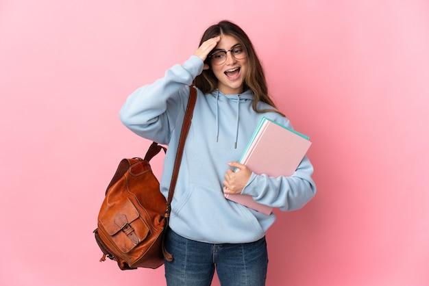 Mulher jovem estudante isolada na parede rosa com expressão de surpresa