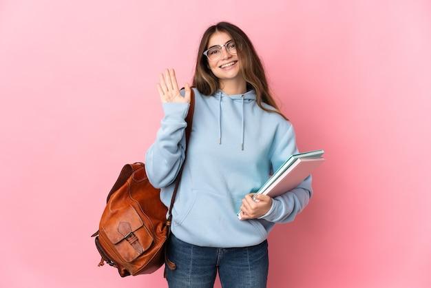 Mulher jovem estudante isolada na parede rosa saudando com a mão com expressão feliz
