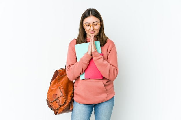 Mulher jovem estudante isolada no branco bakcground de mãos dadas orar perto da boca, sente-se confiante.