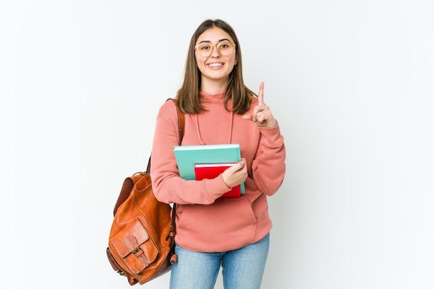 Mulher jovem estudante isolada no branco bakcground indica com os dois dedos anteriores mostrando um espaço em branco.