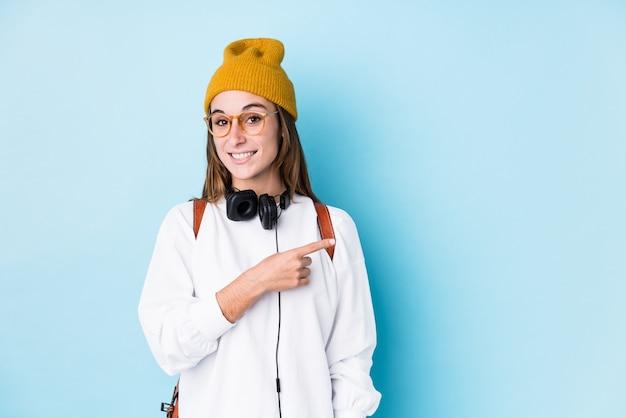 Mulher jovem estudante isolada sorrindo e apontando de lado, mostrando algo no espaço em branco.