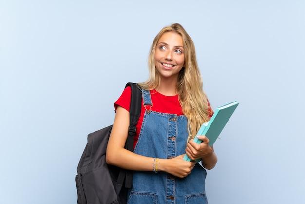 Mulher jovem estudante loira sobre parede azul isolada, rindo e olhando para cima
