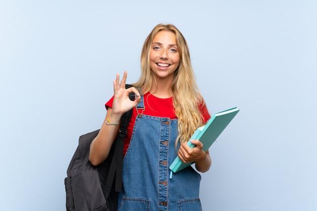 Mulher jovem estudante loira sobre parede azul, mostrando um sinal de ok com os dedos
